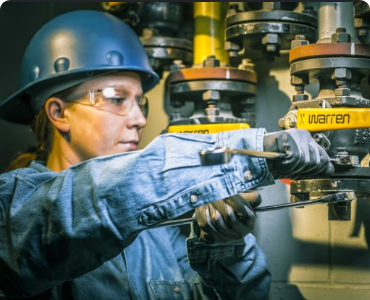 female construction worker tightening pipes